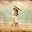Couple kissing under umbrella at the beach — Stock Photo