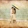 Couple kissing under umbrella at the beach — Stock Photo #11651485