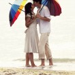 Couple kissing under umbrella at the beach — Stock Photo #11651581