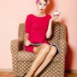 Royalty-Free Stock Photo: Style girl in red dress sitting in armchair with cake and magazi
