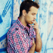 Royalty-Free Stock Photo: Young teen boy smoking near graffiti wall.