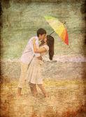 Coppia baciarsi sotto un ombrellone in spiaggia — Foto Stock