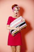 Style redhead girl with shopping box at pink background. — Stock Photo