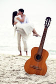 Couple kissing at the beach and guitar. — Stock Photo