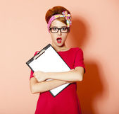 Style redhead girl in glasses and board at pink background. — Stock Photo