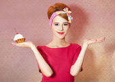 Style redhead girl with cake at pink background. — Stock Photo