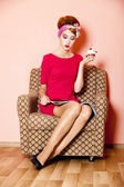 Style girl in red dress sitting in armchair with cake and magazi — Stock Photo