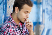 Young teen boy smoking near graffiti wall. — Stock Photo
