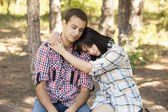 Sad young teenage couple in green park. — Stock Photo
