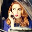 Beautiful redhead businesswoman calling by phone in the car. - Stock Photo