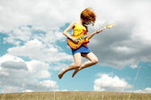 Redhead girl jumping with guitar at outdoor. — Stock Photo