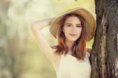 Redhead girl with hat near tree. — Stock Photo