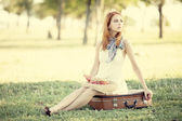 Redhead girl sitting at bag at outdoor. — Stock Photo