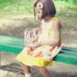 Child sit on the bench in the park. — Stock Photo
