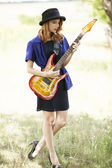 Style redhead girl with guitar at outdoor. — Stock Photo
