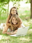 Two sisters with laptop in the park. — Stock Photo
