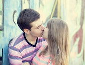 Young couple kissing near graffiti background. — Stock Photo