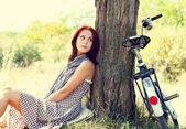 Beautiful girl sitting near bike and tree at rest in forest. Pho — Stock Photo