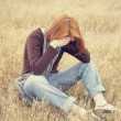 Lonely sad red-haired girl at field — Stock Photo #12254704