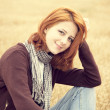 Beautiful red-haired girl at yellow autumn grass. — Stock Photo #12254712