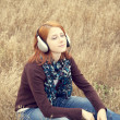Young smiling girl with headphones at field. — Stock Photo #12254719