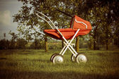 Toy pram in orchard — Stock Photo