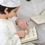 Muslim Arabic father and son recitating Koran — Stock Photo