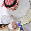 Muslim Arabic father and son reading Koran — Stock Photo