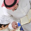 Muslim Arabic father and son reading Koran — Stok fotoğraf