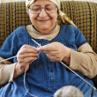Image of an old arabic woman sitting on a sofa and knitting - Stock Photo