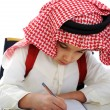 Arabian kid writing on the table — Stock Photo