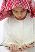 Muslim Arabic little boy reading Koran — Stock Photo