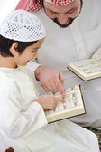 Muslim Arabic father and son recitating Koran — Stock Photo