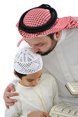 Middle eastern education, father kissing son while reading Koran — Stock Photo