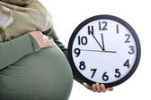 Tummy of pregnant muslim woman with clock — Stock Photo