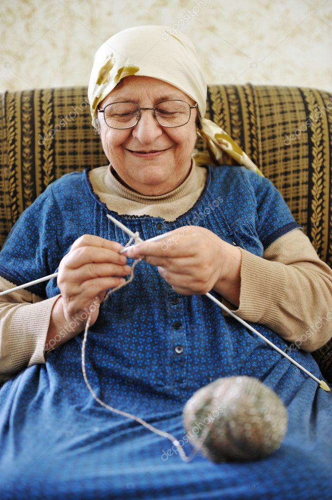 Old Knitting Woman : Image of an old arabic woman sitting on a sofa and