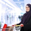 Image of pretty muslim woman with cart looking at camera — Stock Photo