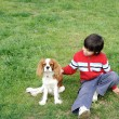 Stock Photo: Young boy playing with a dog