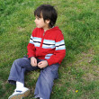 Alone kid boy is sitting on the grass — Stock Photo