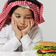Unhappy Arabic kid with burger — Stock Photo #11751109