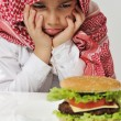 Angry Arabic kid with burger — Stock Photo #11751113