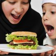 Royalty-Free Stock Photo: Arabic little male and female eating Burger