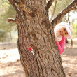 Arabic Muslim girl in nature, hiding behing the tree — Stock Photo