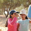Stock Photo: Children having picnic in scout camp in nature, girls drinking water
