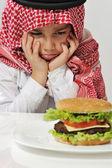 ハンバーガーと一緒に怒っているアラビア語キッド — ストック写真