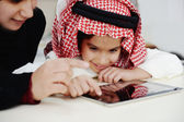 Arabic little boy and his mother working with touch tablet — Stock Photo