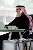 Portrait of a smart arabic business man using laptop and talking on the phone — Stock Photo