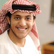 Smiling young success man, arabic clothes, education concept, indoor, school or university, student or teacher. — Stock Photo #12095653