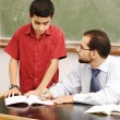 Male teacher in classroom helping a pupil in front of the board — Stock Photo #12095890
