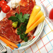 Sliced meat with sauce on board with vegetables — Stock Photo